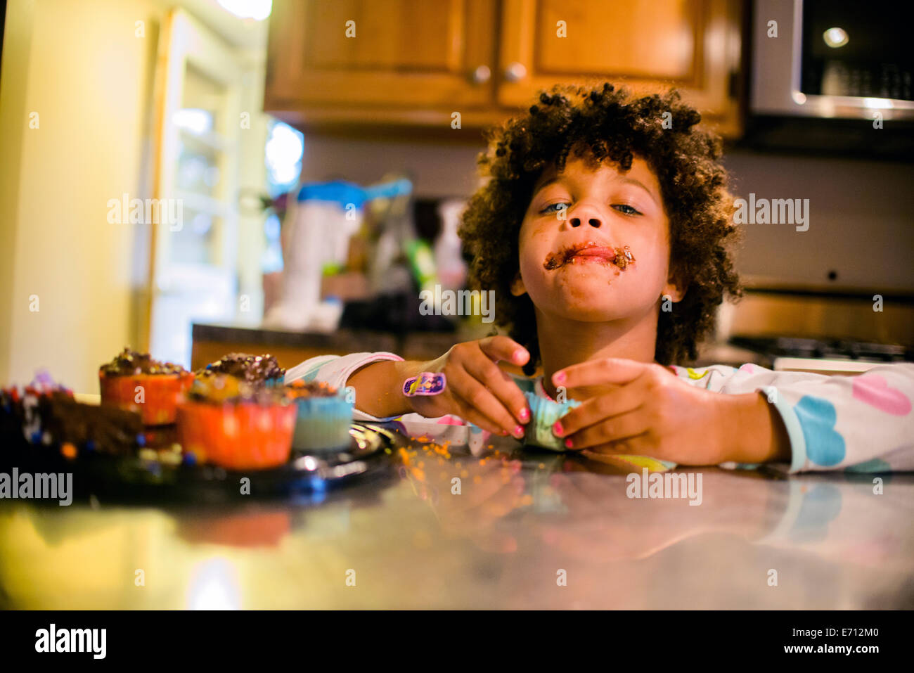 Portrait of girl with chocolate covered mouth eating cupcakes - Stock Image