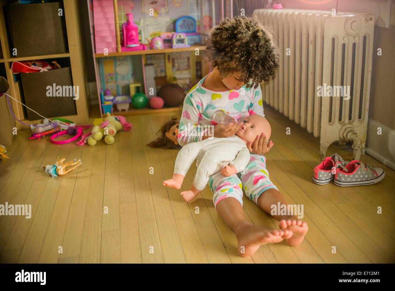 Girl sitting on playroom floor feeding doll - Stock Image