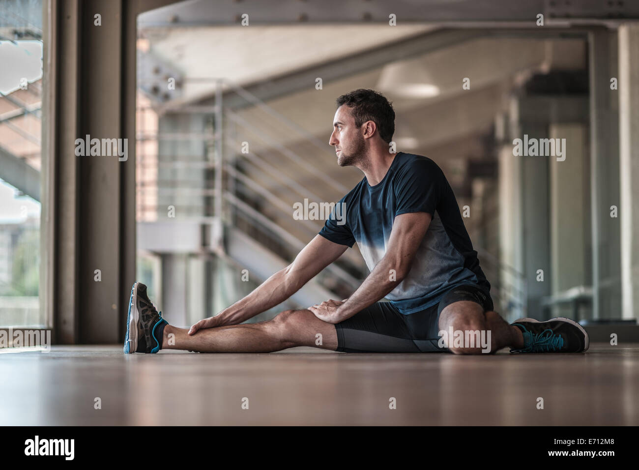 Mid adult man stretching - Stock Image