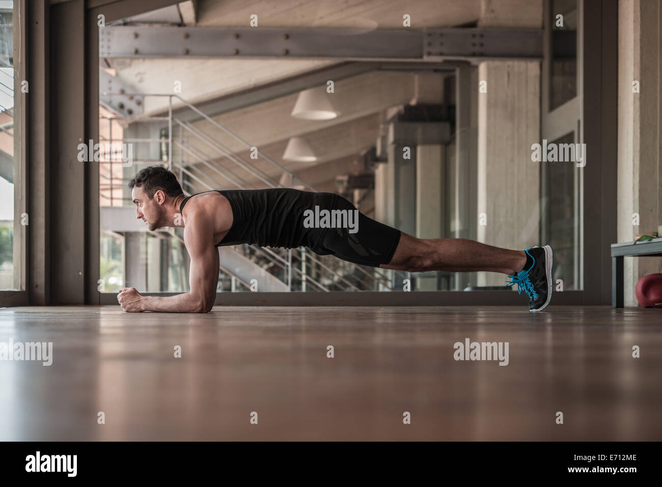 Mid adult man doing plank exercise - Stock Image