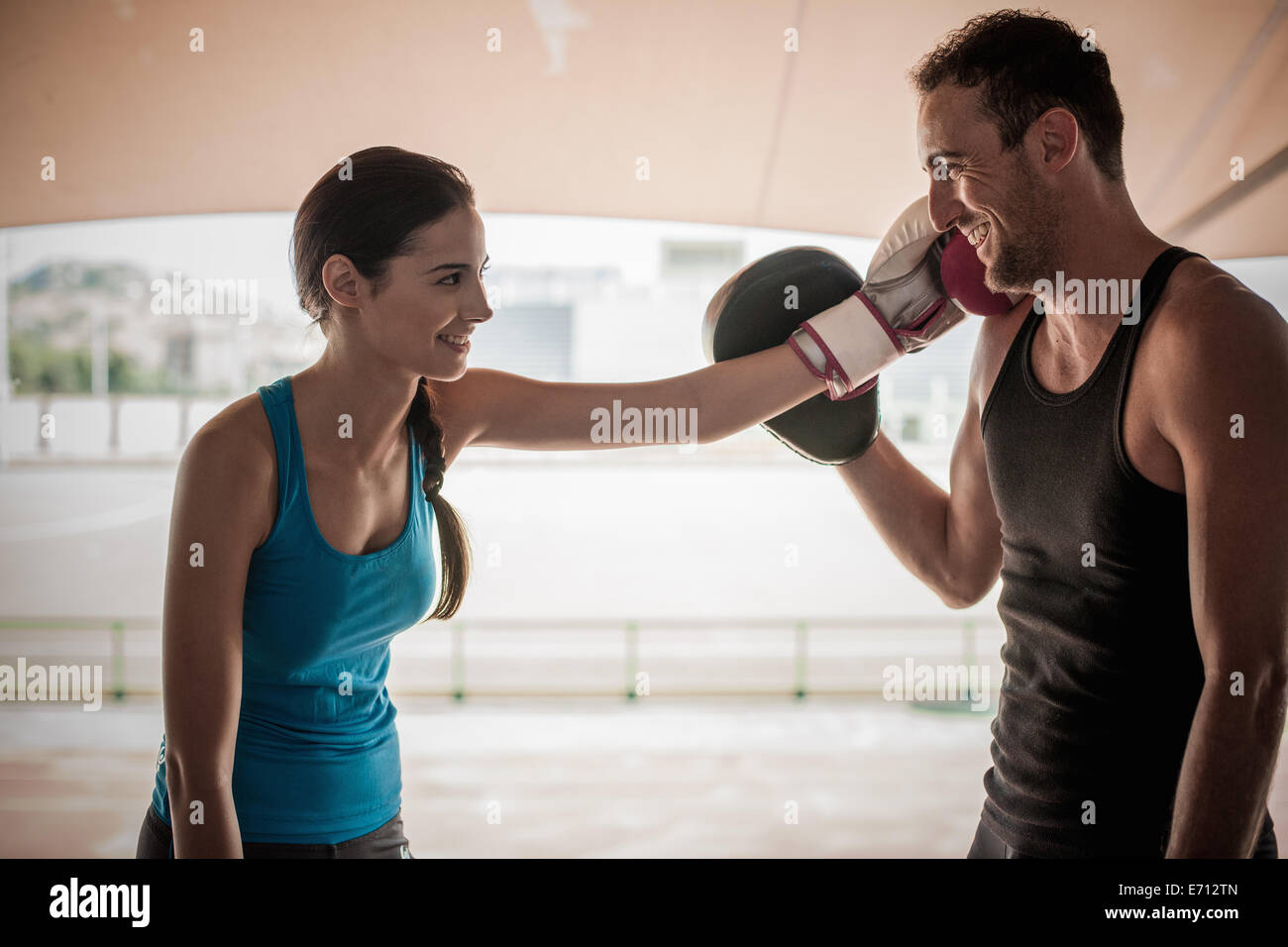 Young woman wearing boxing glove touching man's face - Stock Image