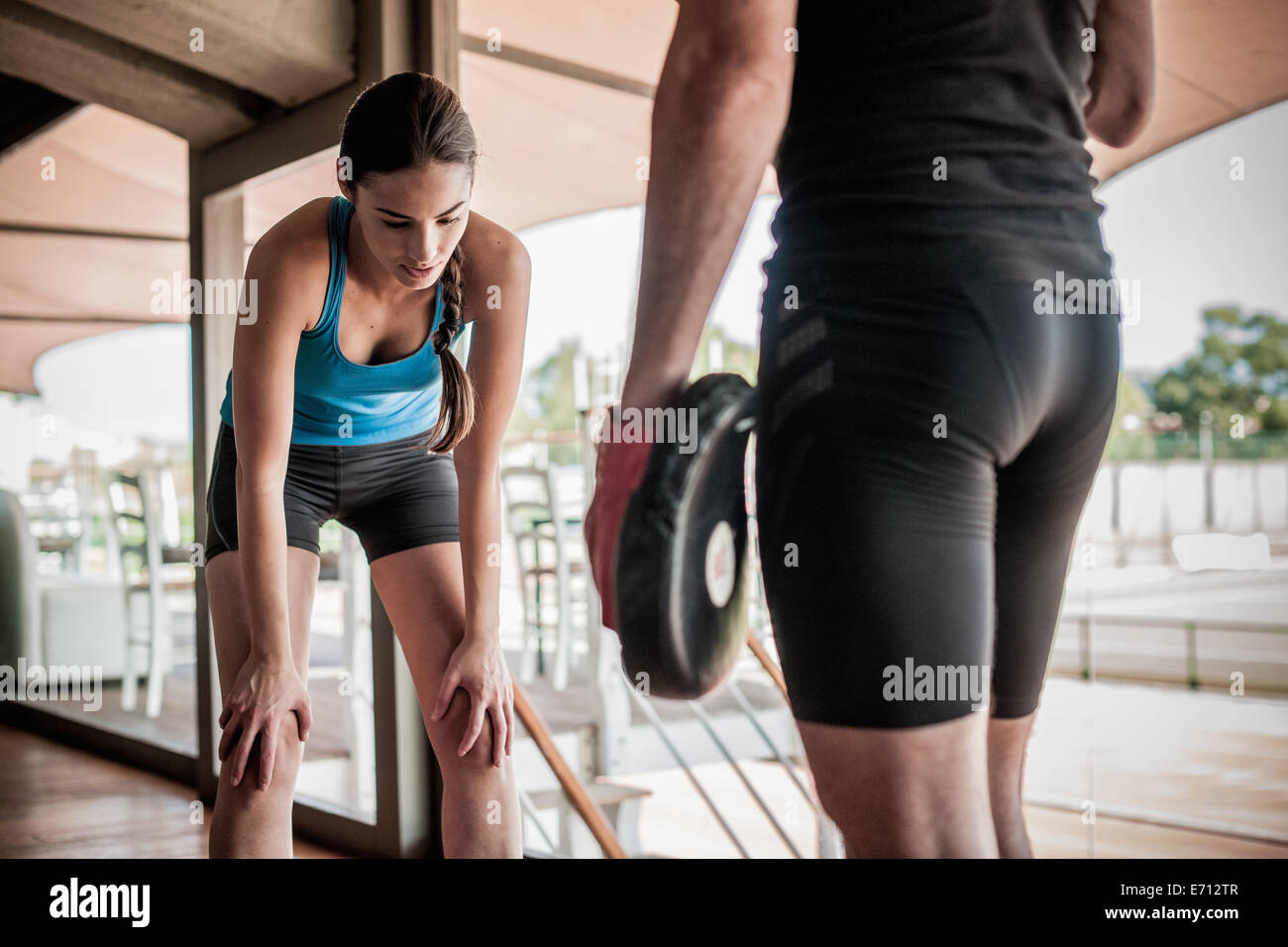 Young woman bending forwards, resting - Stock Image