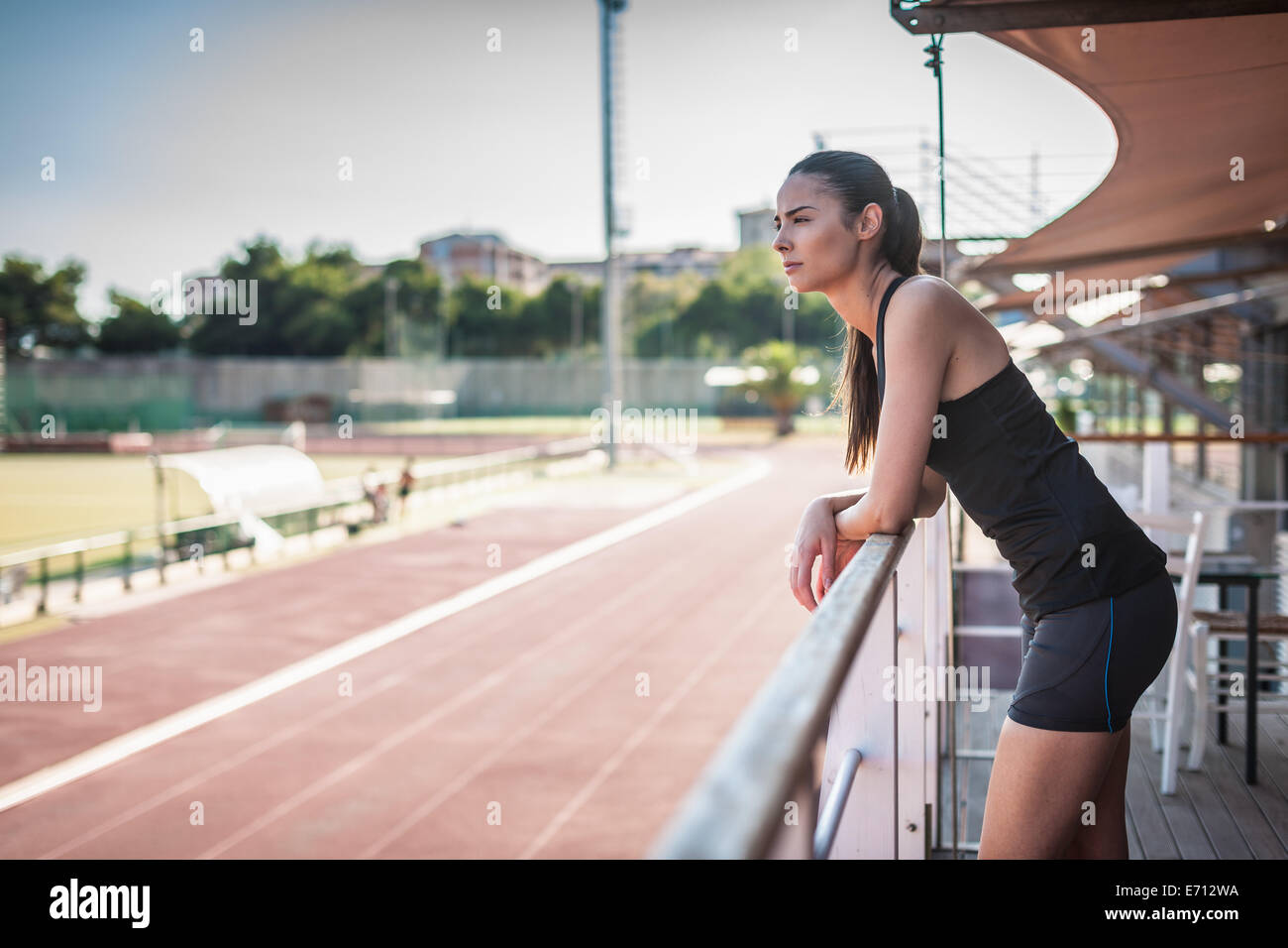 Young woman leaning on railing by race track - Stock Image