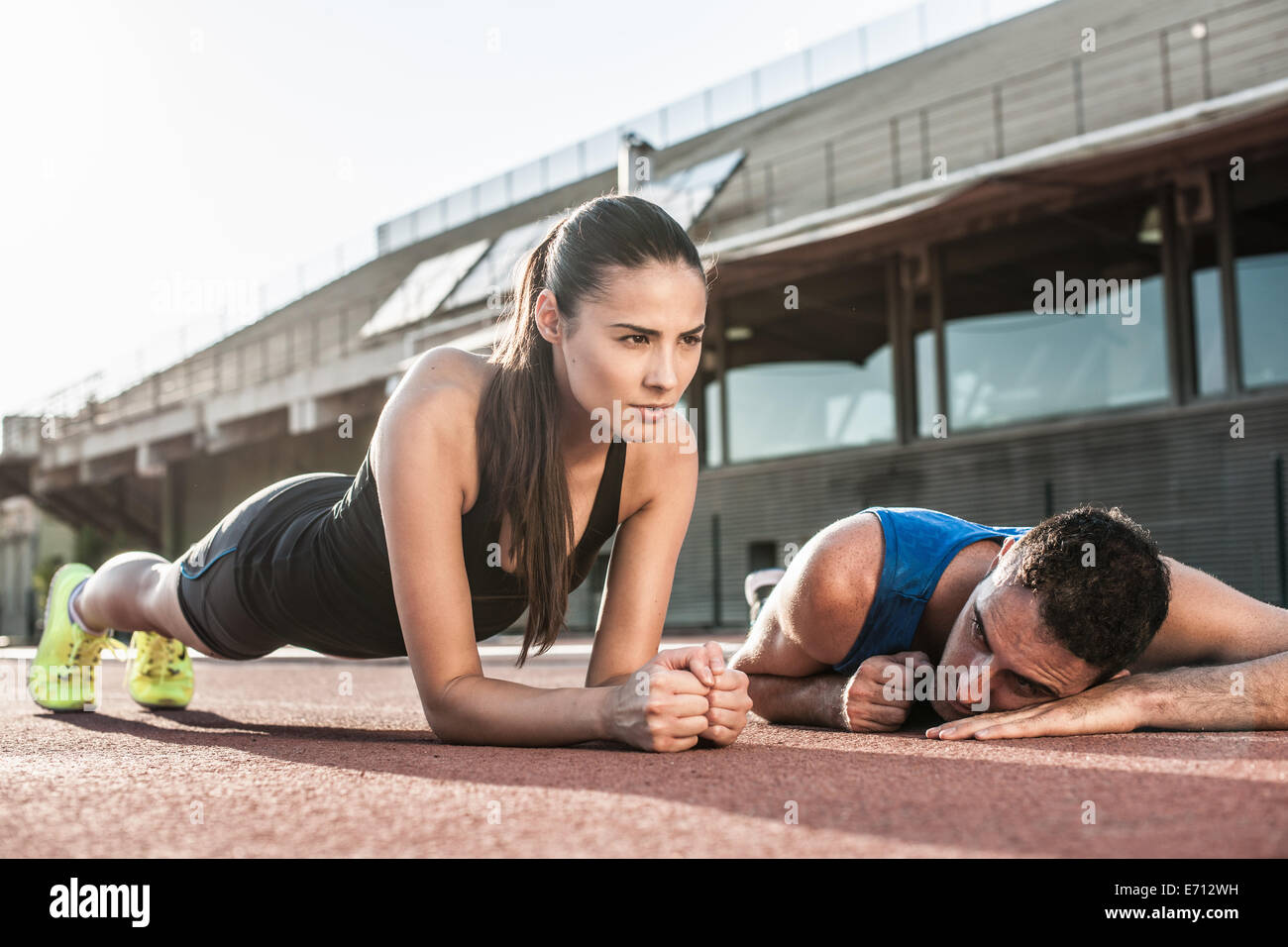 Woman doing plank exercise, man resting on floor - Stock Image