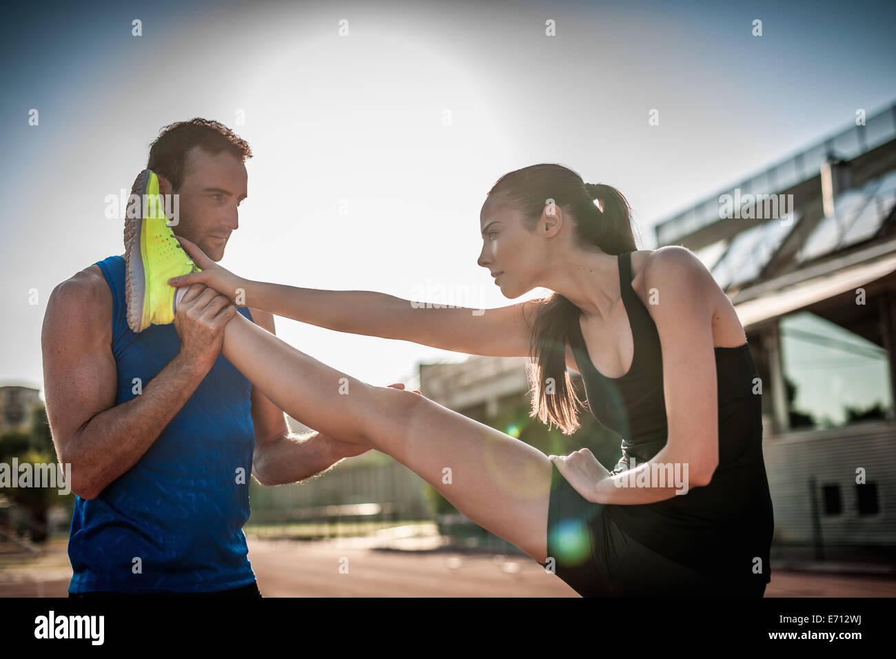 Man helping woman stretch leg - Stock Image