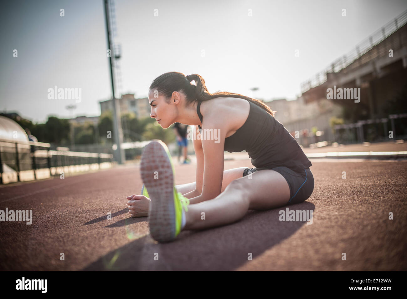Woman sitting on floor stretching legs - Stock Image