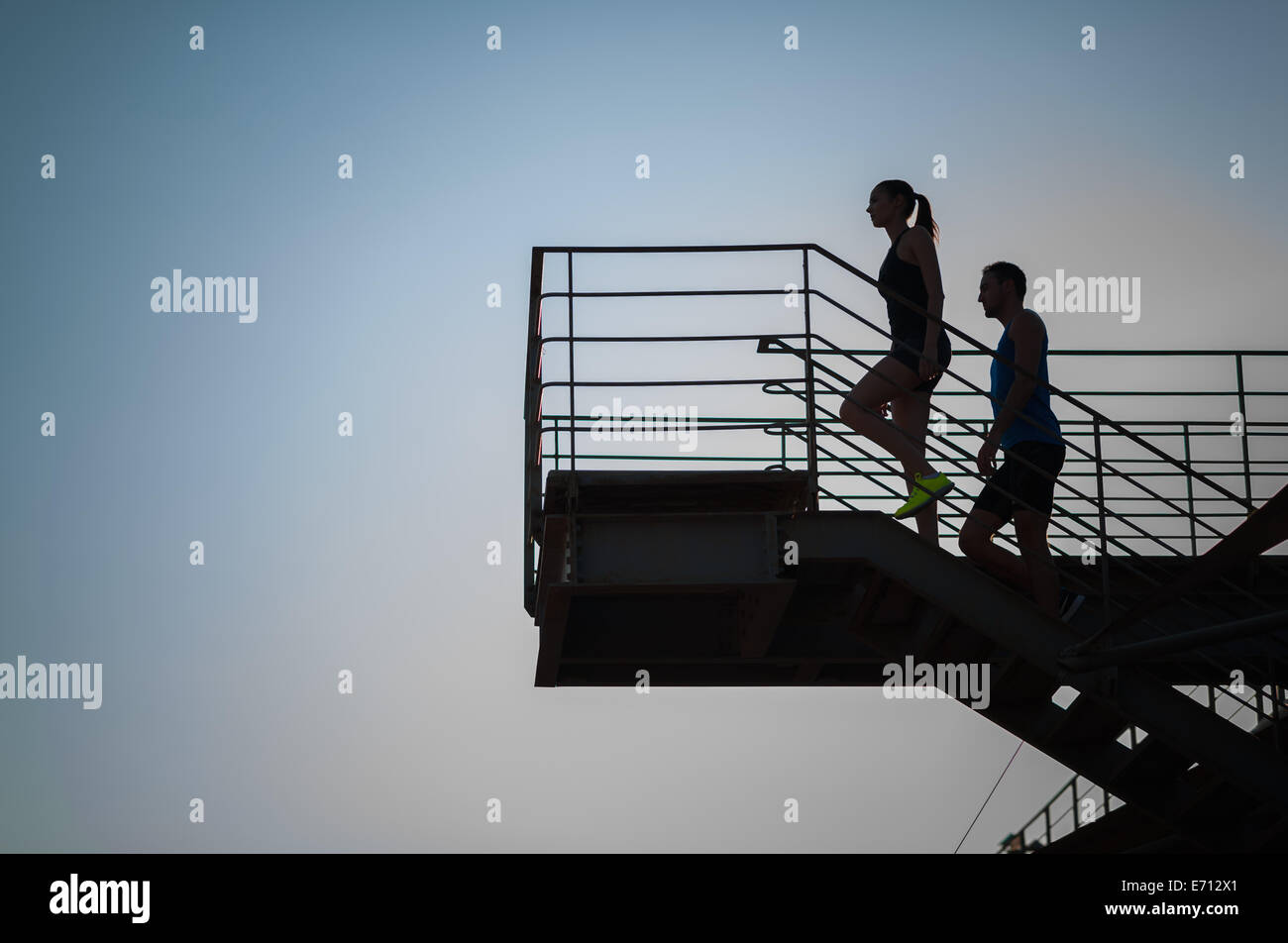 Man and woman going up steps, silhouette - Stock Image