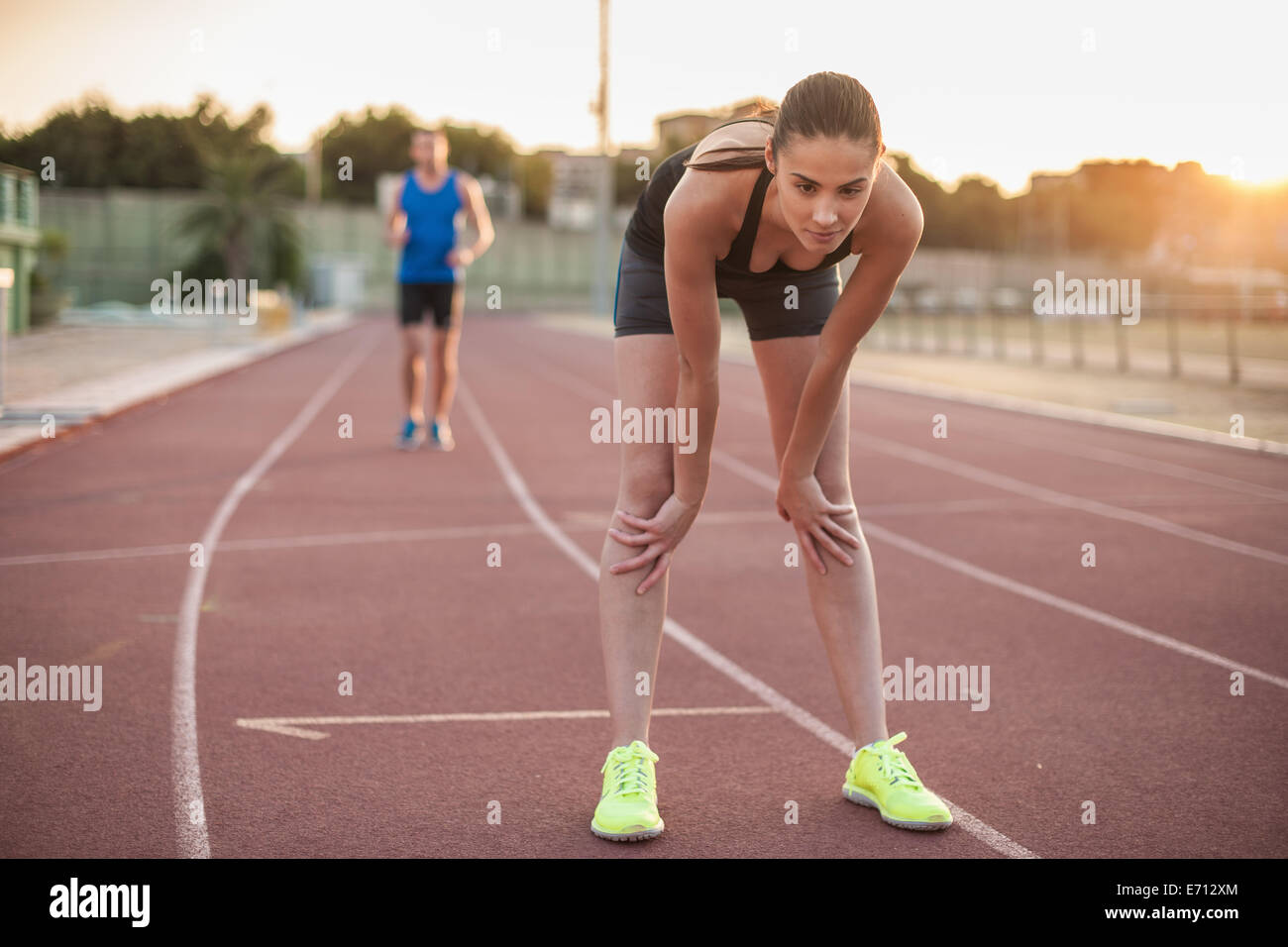 Woman leaning forward on racing track - Stock Image