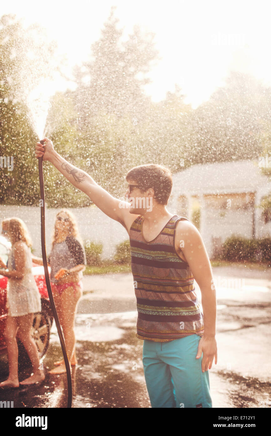Young man spraying water with hosepipe - Stock Image