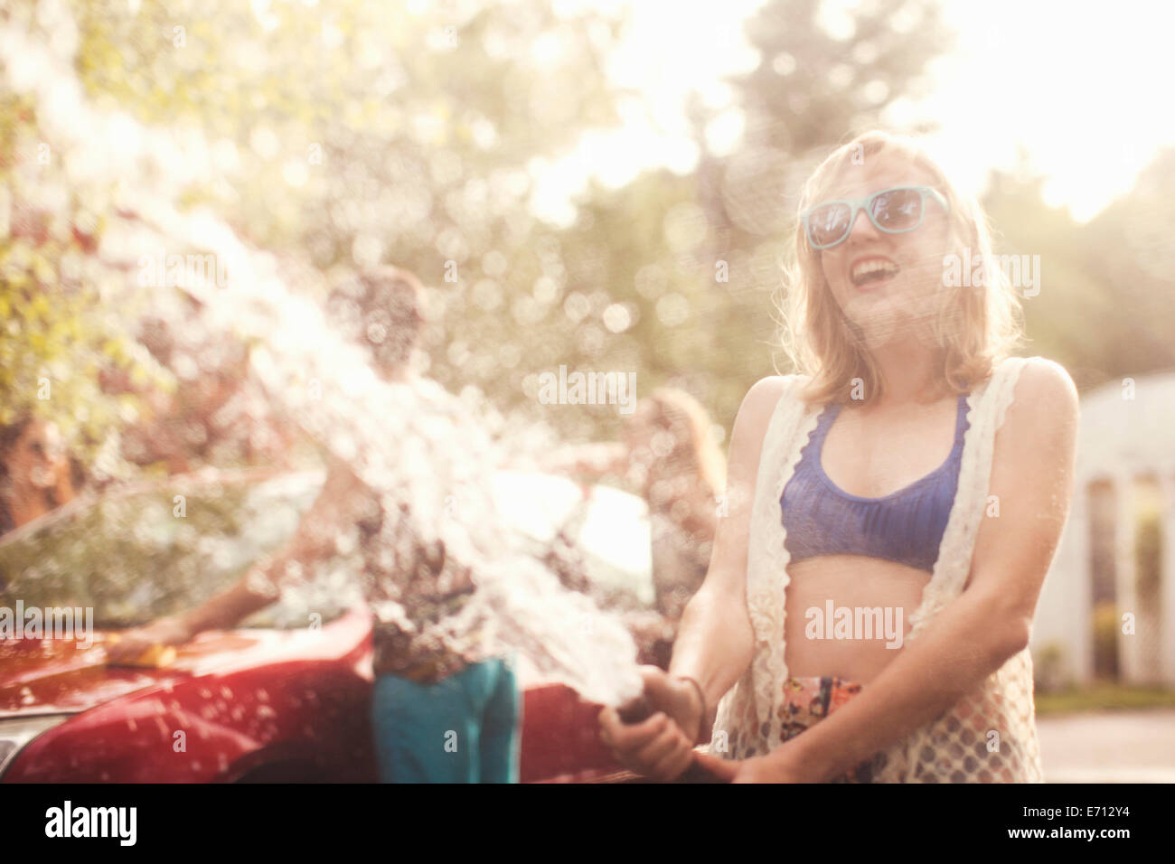 Young woman spraying water from hosepipe Stock Photo