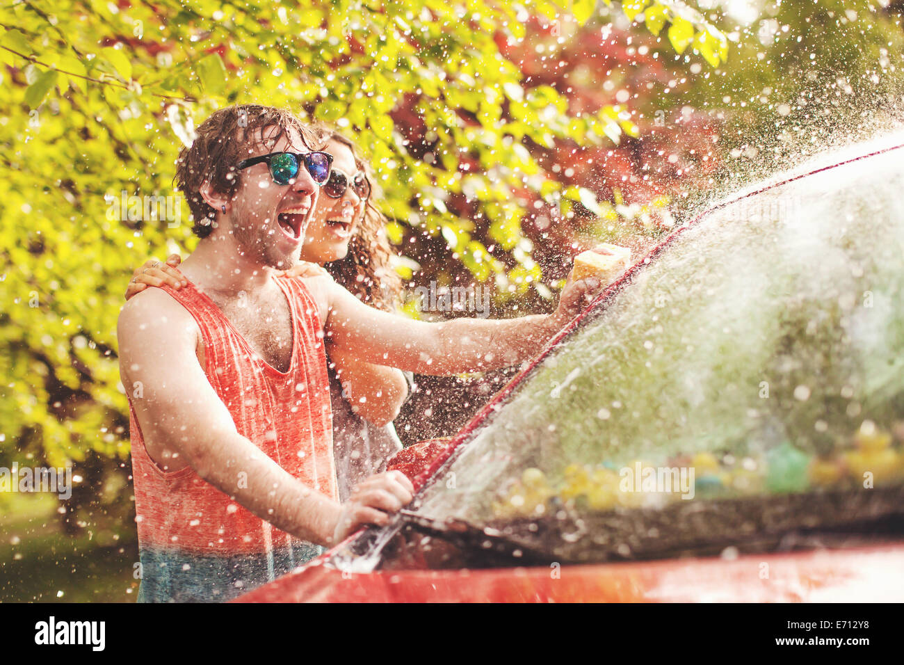 Young couple washing car - Stock Image