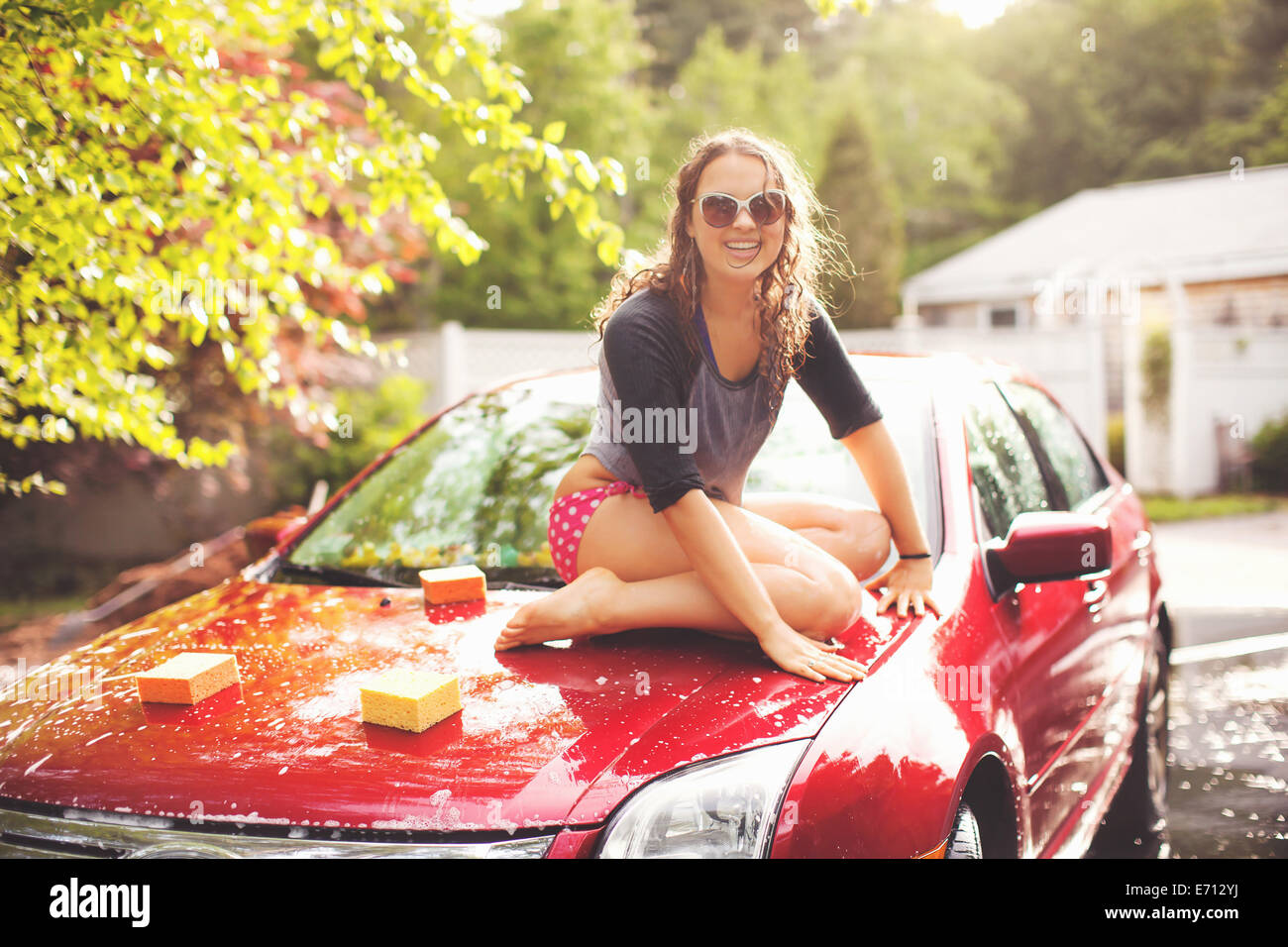 Young woman sitting on car bonnet, portrait - Stock Image