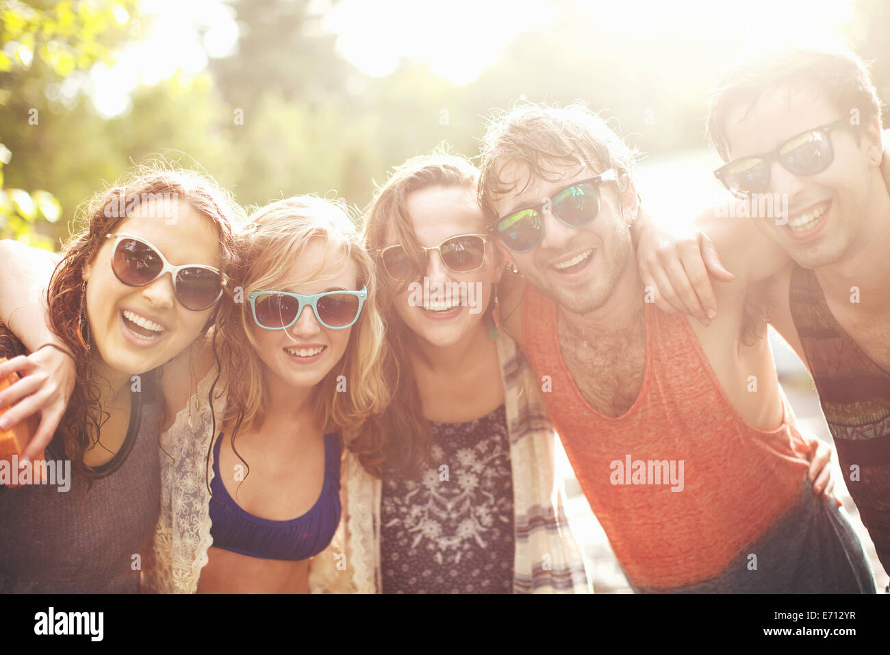 Five friends with arms around each other, portrait - Stock Image