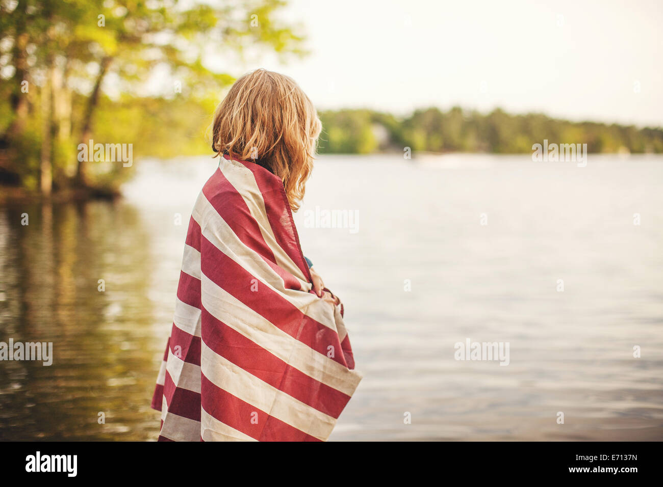 Young woman wrapped in red and white striped fabric - Stock Image