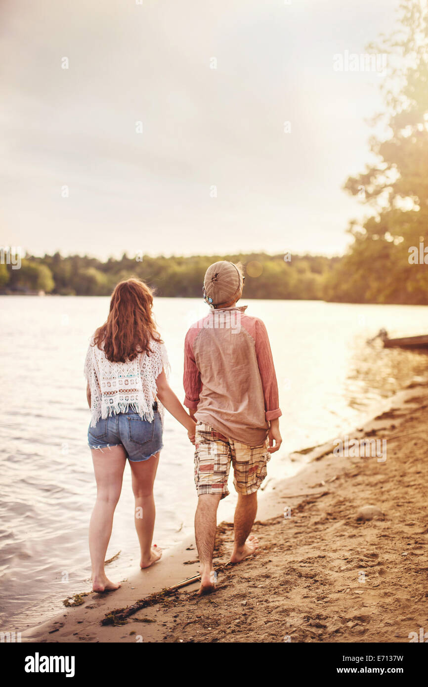 Young couple walking on beach holding hands - Stock Image