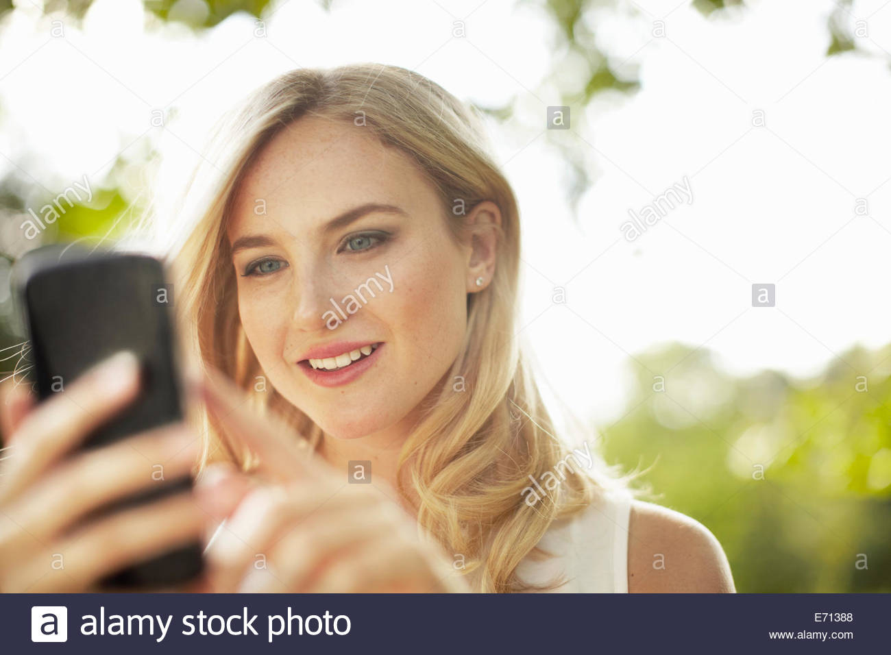 Young woman using smartphone touchscreen in park - Stock Image