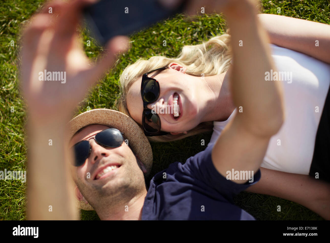 Couple lying in park taking selfie on smartphone Stock Photo