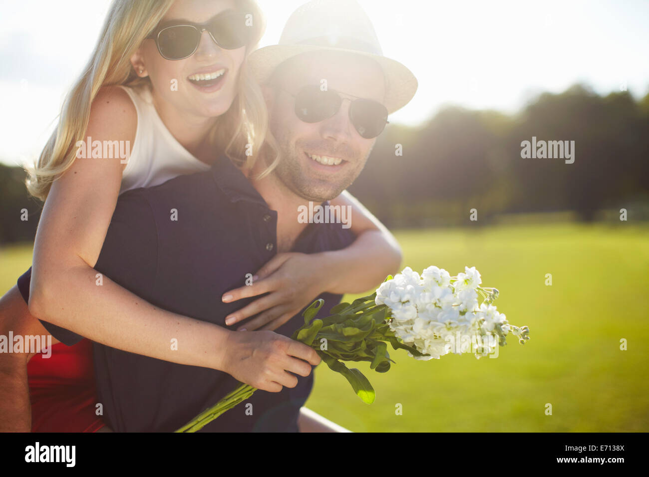 Young woman with flowers getting piggy back from boyfriend in park - Stock Image