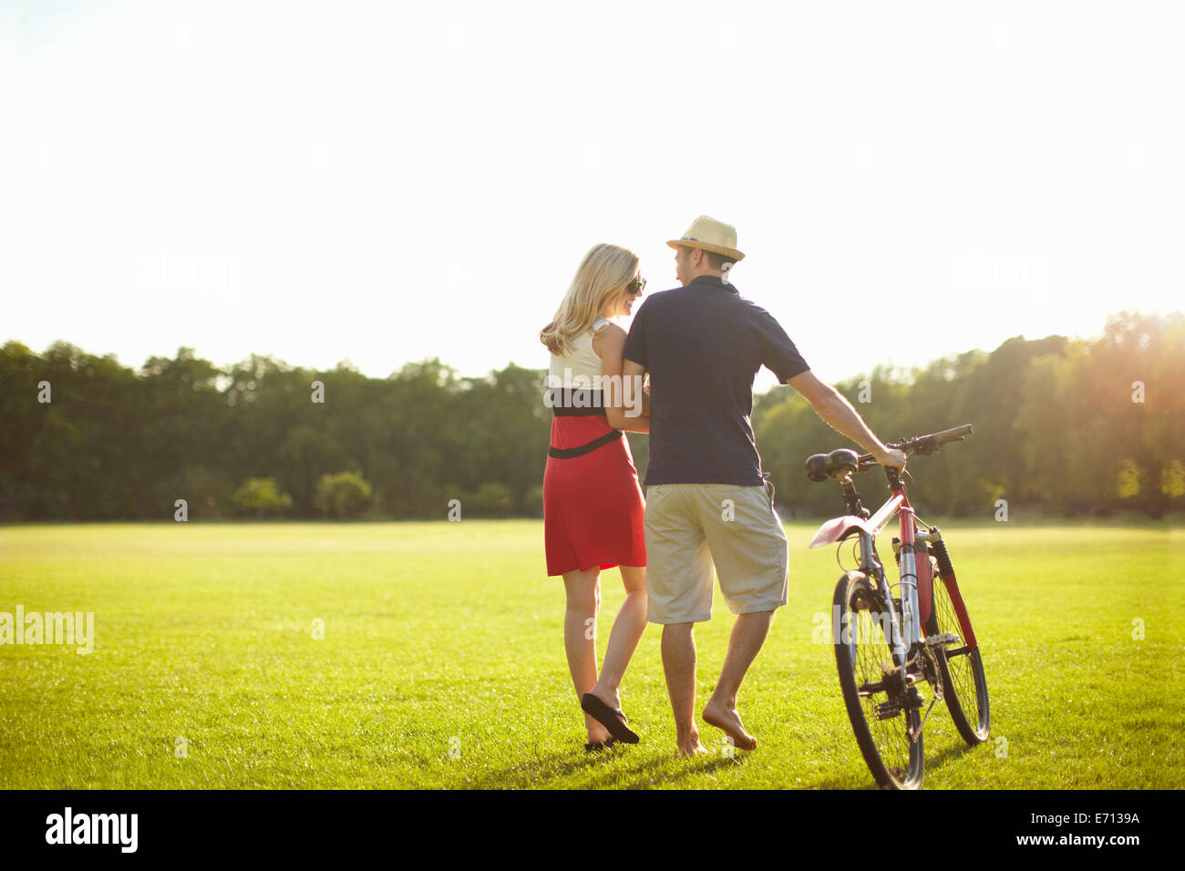 Couple pushing cycle whilst strolling in park - Stock Image