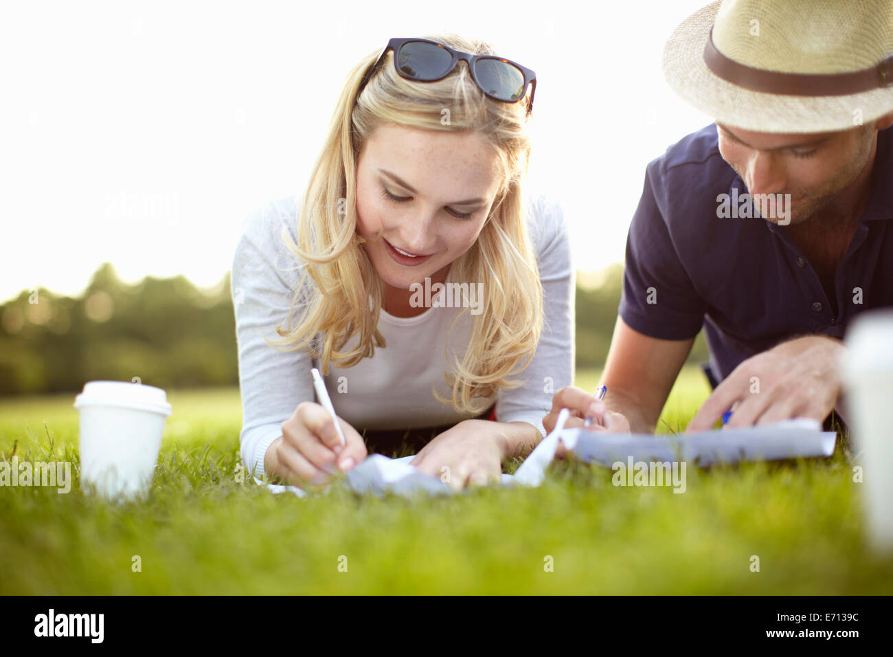 Couple lying in park writing on paper - Stock Image