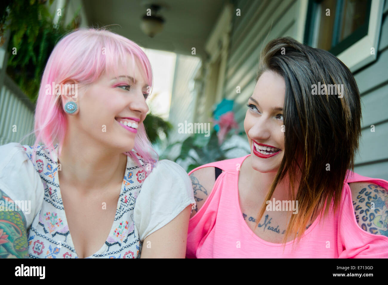 Two funky female friends chatting on porch Stock Photo