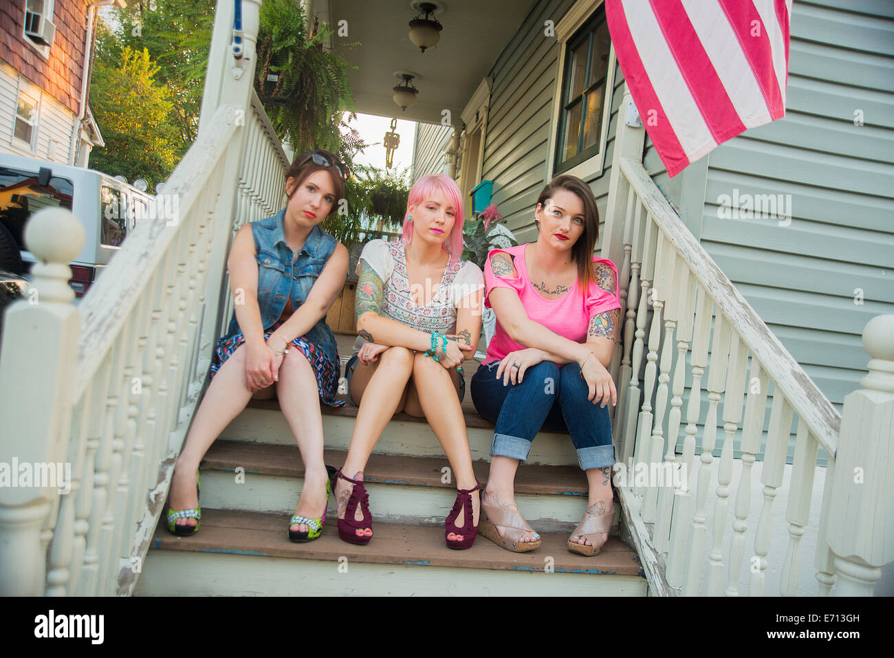 Portrait of young female friends sitting on porch steps - Stock Image