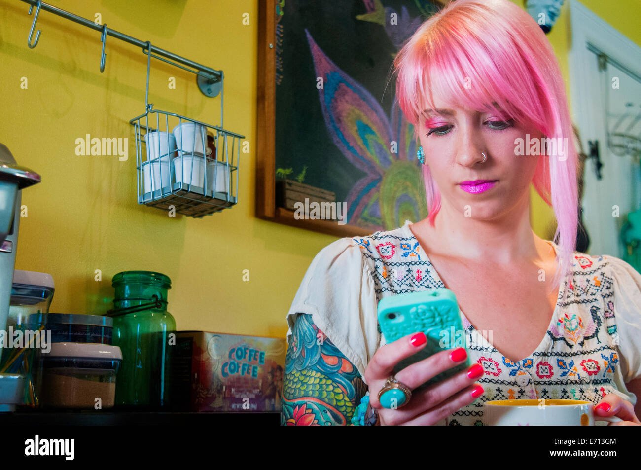 Young woman with pink hair reading text message on smartphone in kitchen - Stock Image