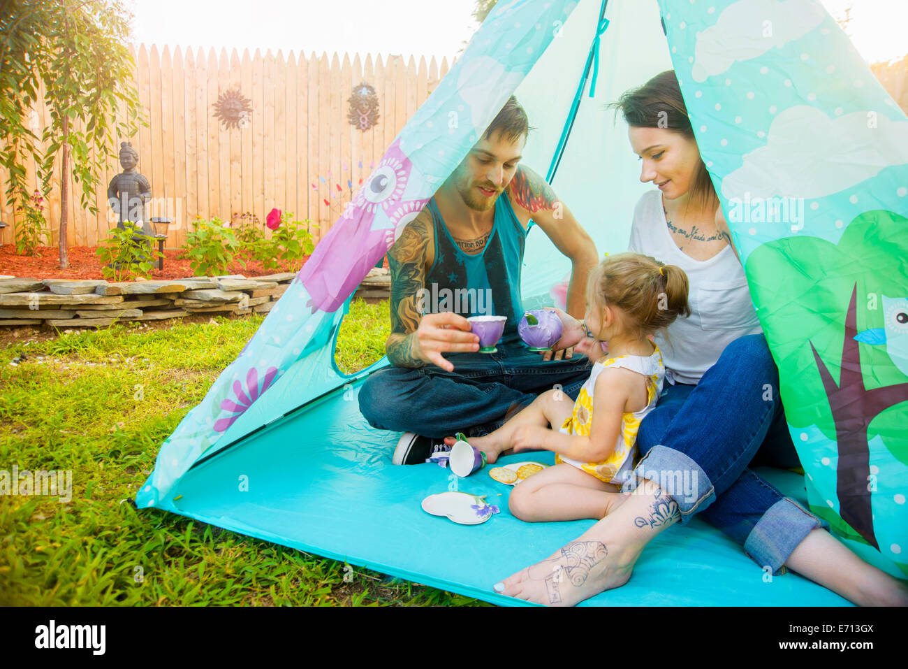 Young couple and toddler daughter playing teatime in tent - Stock Image