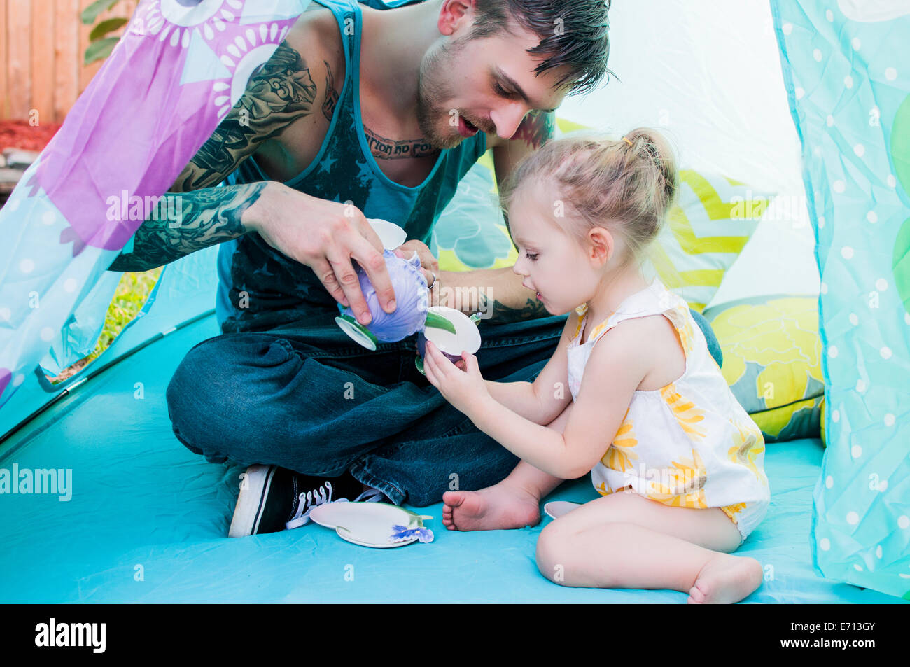 Young man and toddler daughter playing with teacup in tent - Stock Image