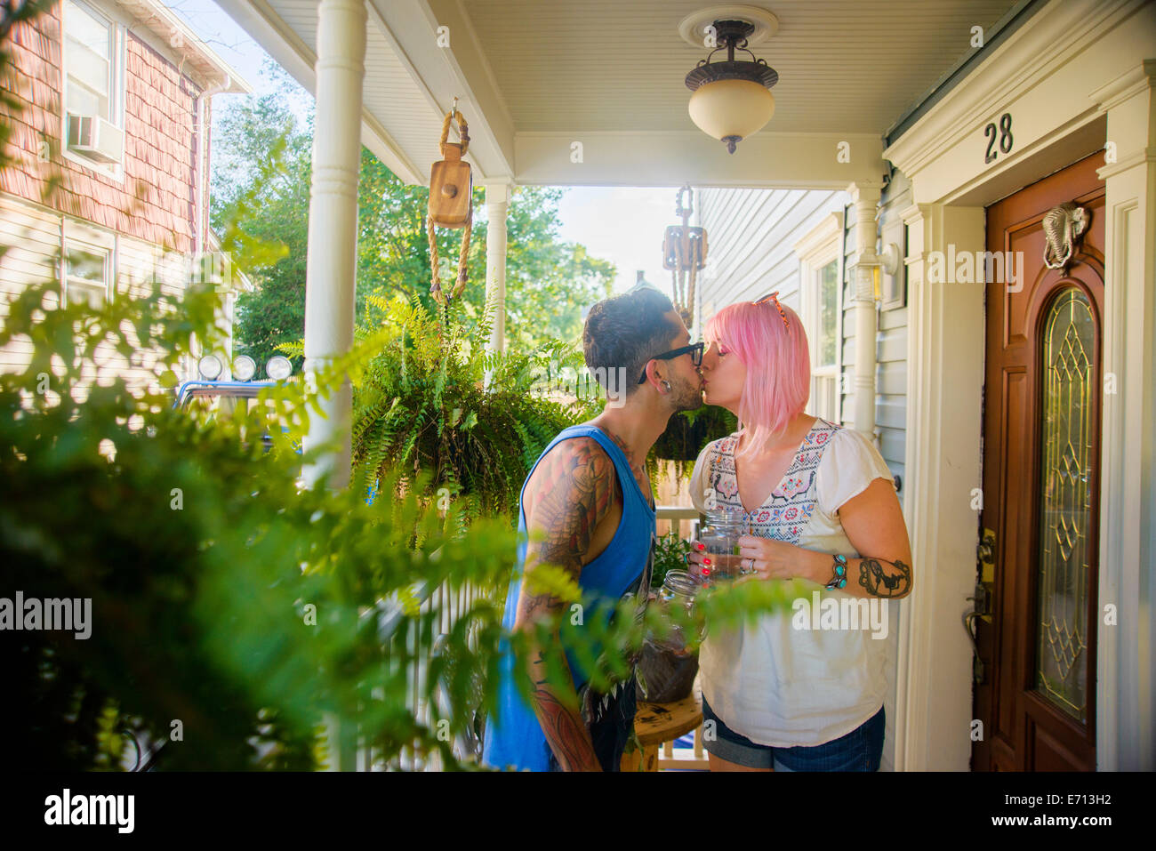 Funky couple kissing on porch Stock Photo