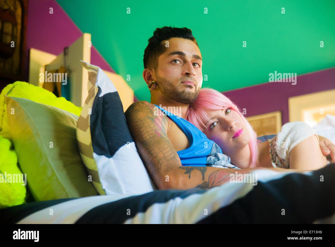 Funky couple reclining and gazing from bed - Stock Image