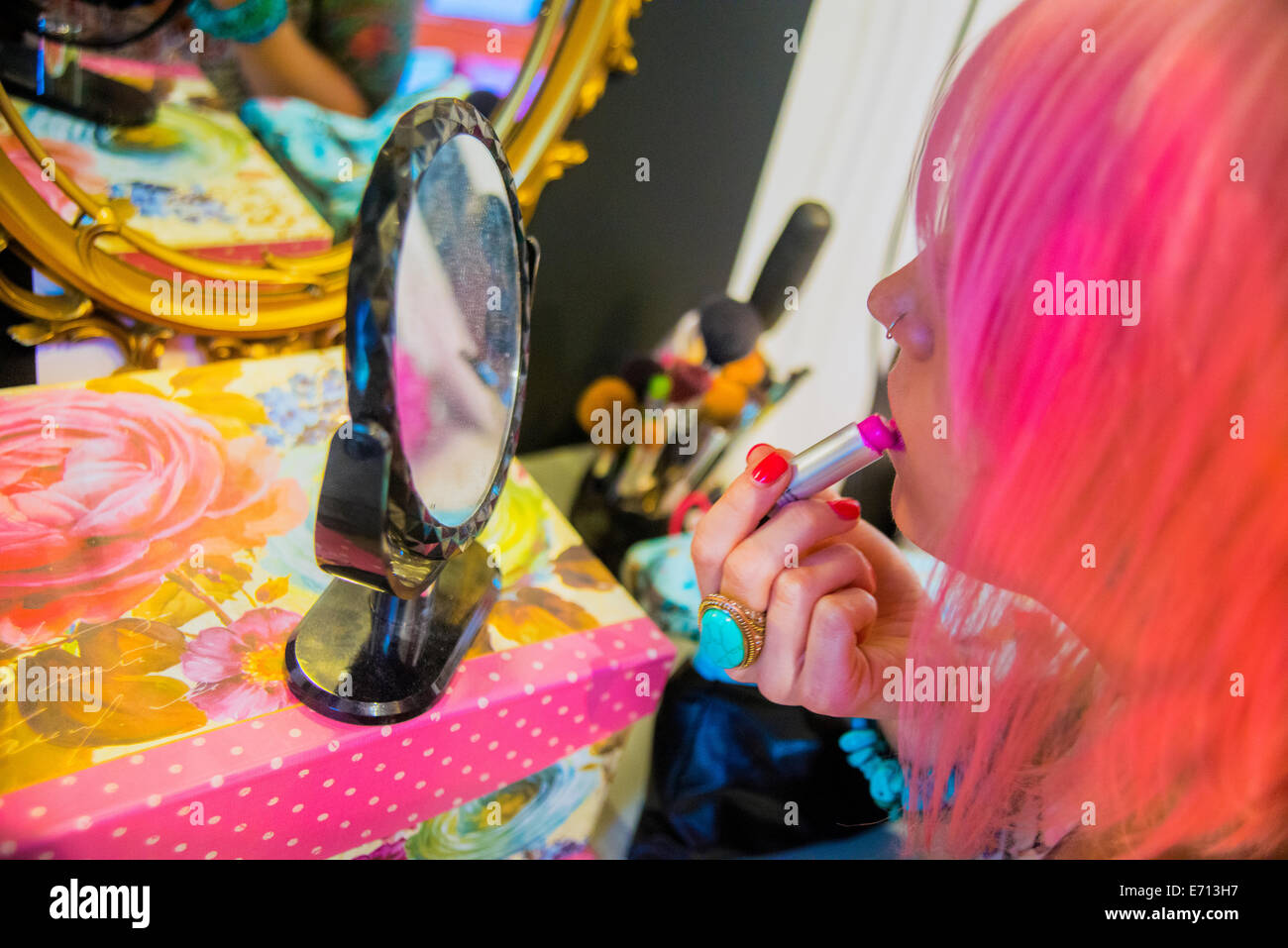 Young woman with pink hair putting on pink lipstick - Stock Image