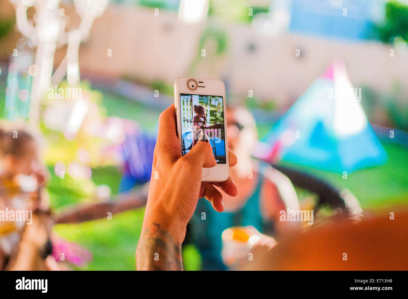 Mid adult man photographing friends on smartphone in garden - Stock Image