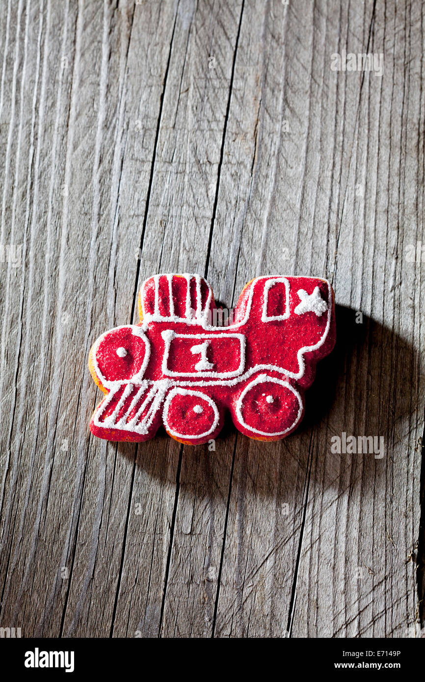 Red-white gingerbread locomotive on grey wood - Stock Image