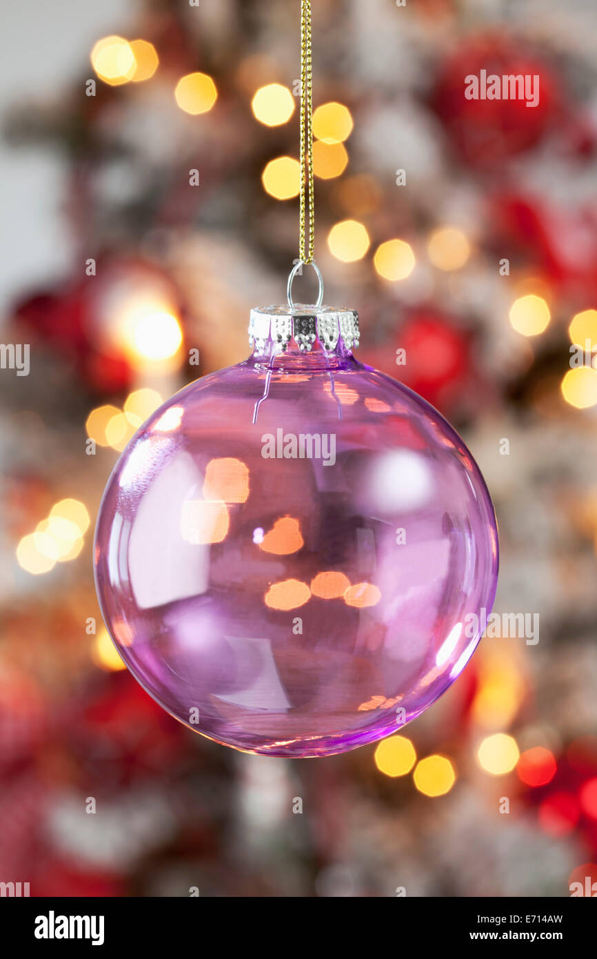 Transparent Christmas bauble hanging in front of blurred flares - Stock Image