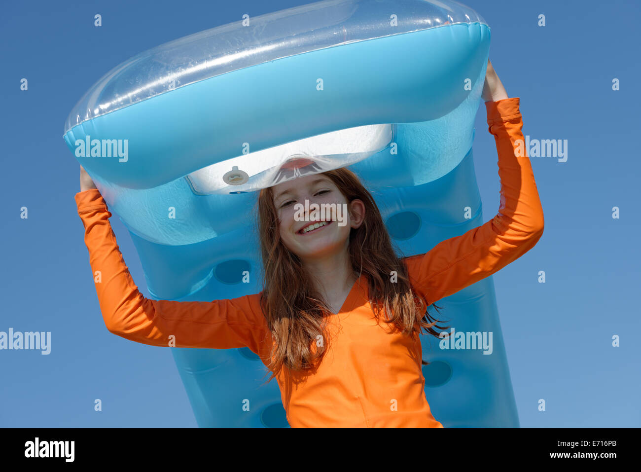 Portrait of smiling girl carrying air mattress on her head wearing sun protection longsleeve - Stock Image