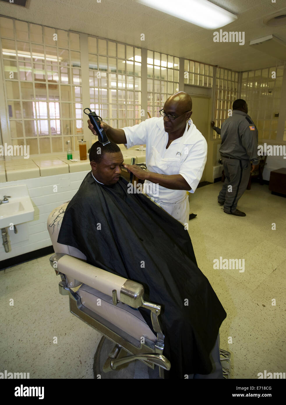 Inmate cuts hair of fellow prisoner at the barber shop inside Darrington Prison, a correctional institution near - Stock Image