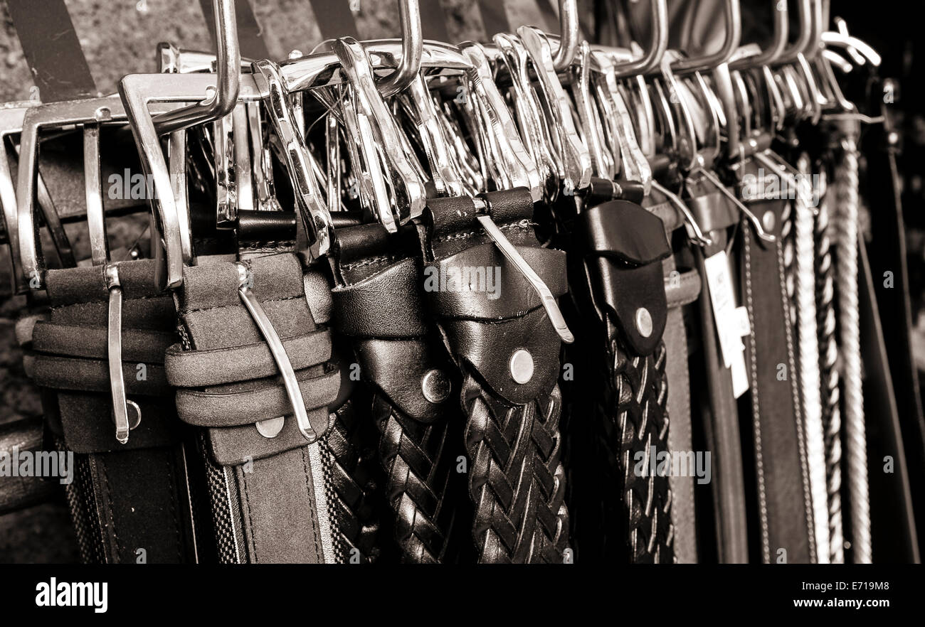 Close up of buckles on leather belts for sale in a shop in Italy. - Stock Image