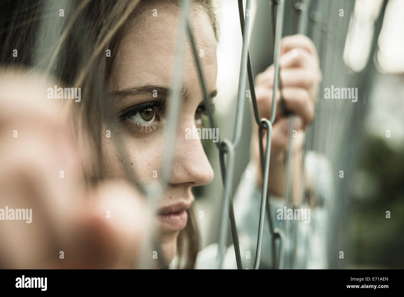 Teenage girl looking through a wire fence - Stock Image