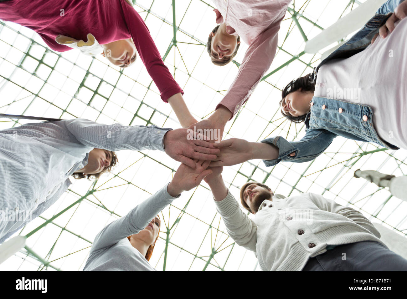 Group of young people stacking their hands - Stock Image
