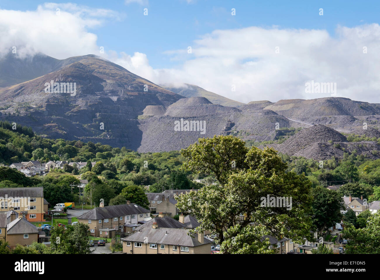 Industrial landscape with Penrhyn slate quarry and spoil heaps above houses in town on edge of Snowdonia National - Stock Image