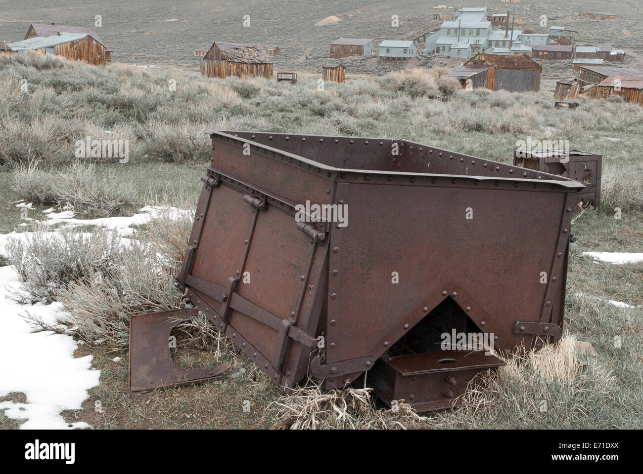 View over an old rusty piece of machinery in melting snow and shrubland to buildings of Bodie, gold rush town in - Stock Image