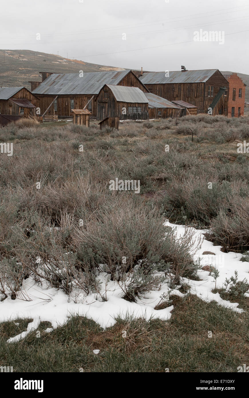 View across melting snow and shrubland to main buildings of Bodie, gold rush town in California - Stock Image