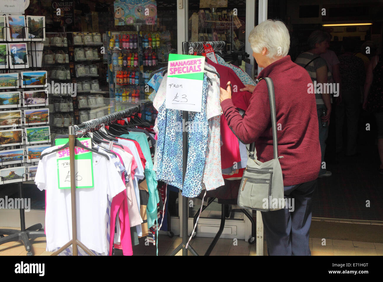 Affluent older lady browsing bargain rail outside a shop in Pitlochry, Scotland - Stock Image