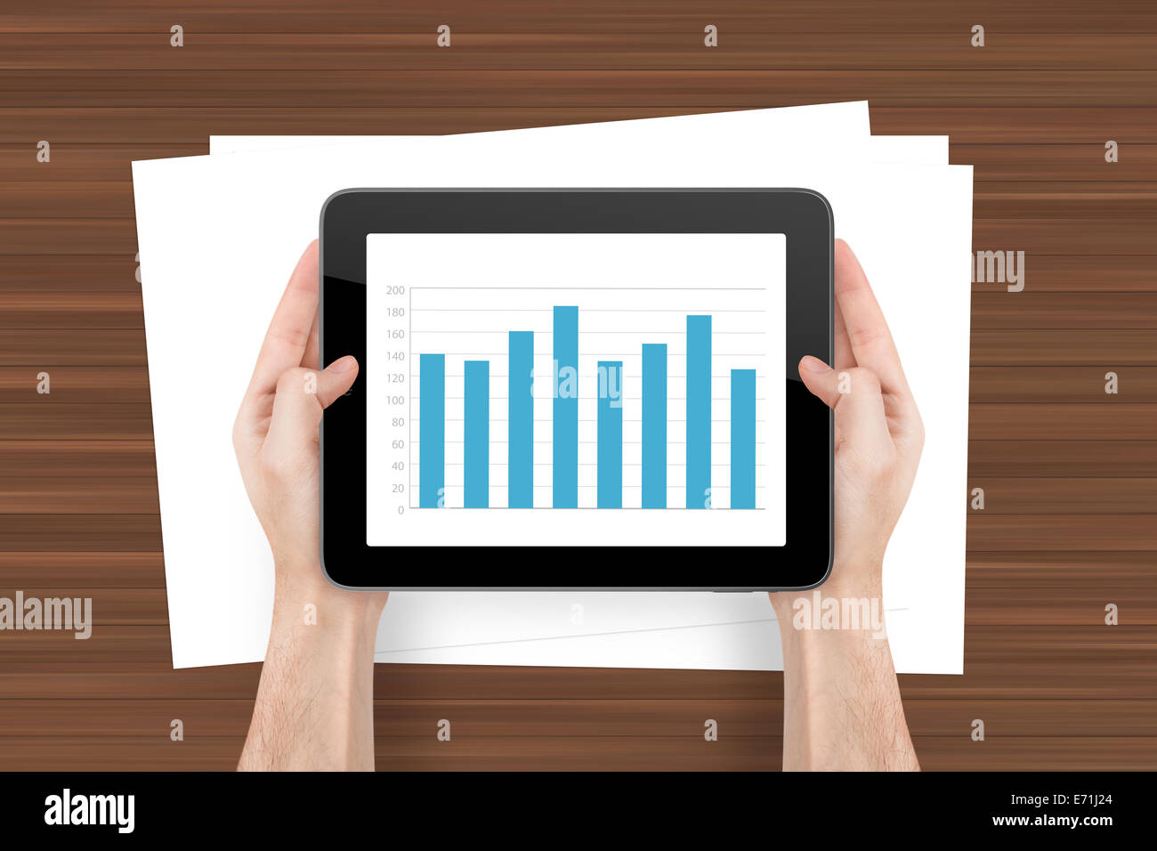 Hand holding digital tablet with bar chart graphic and white, blank note sheet on wooden background. - Stock Image
