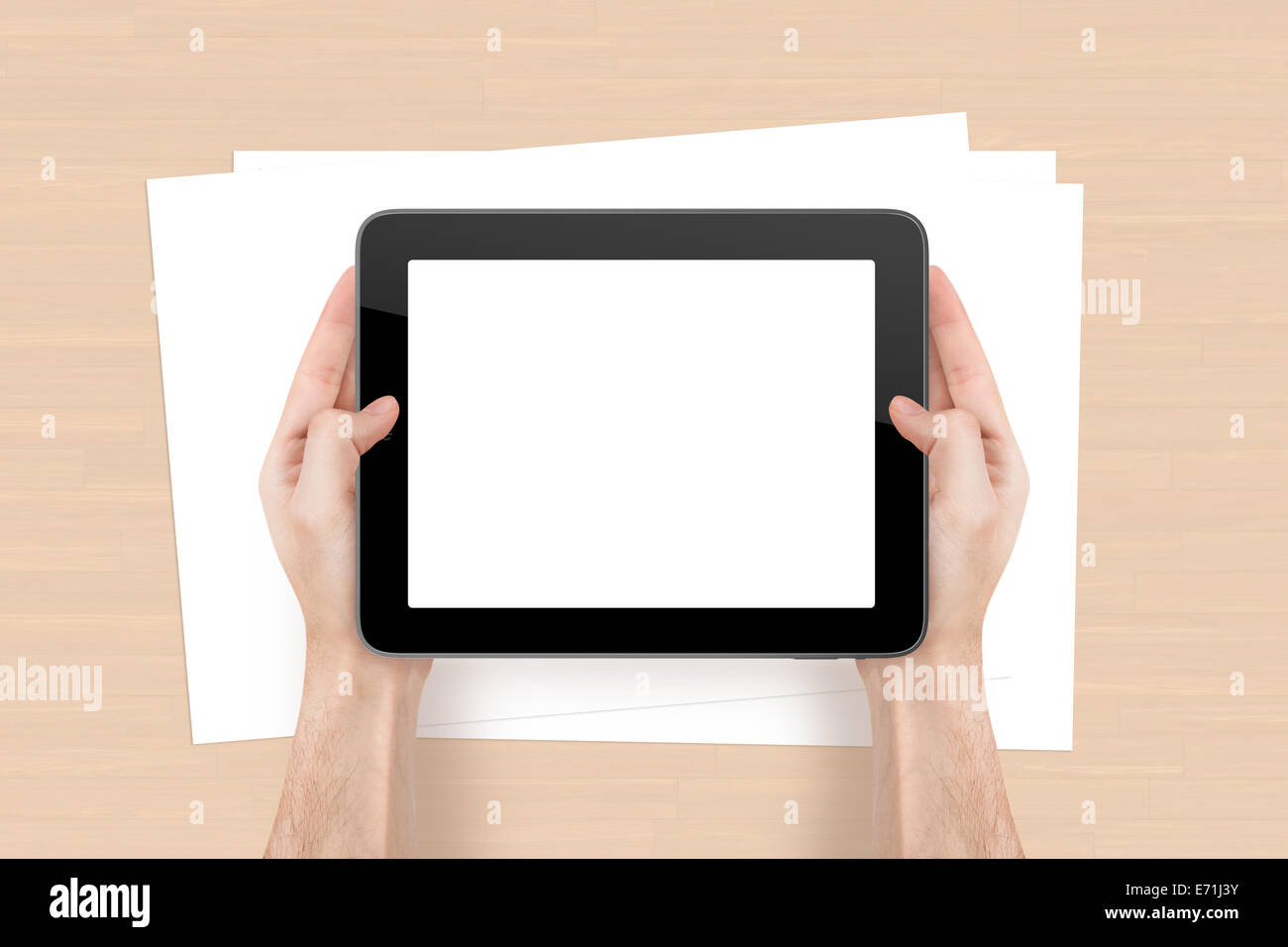 Hand holding tablet with blank, white screen and empty sheet on wooden office table. - Stock Image