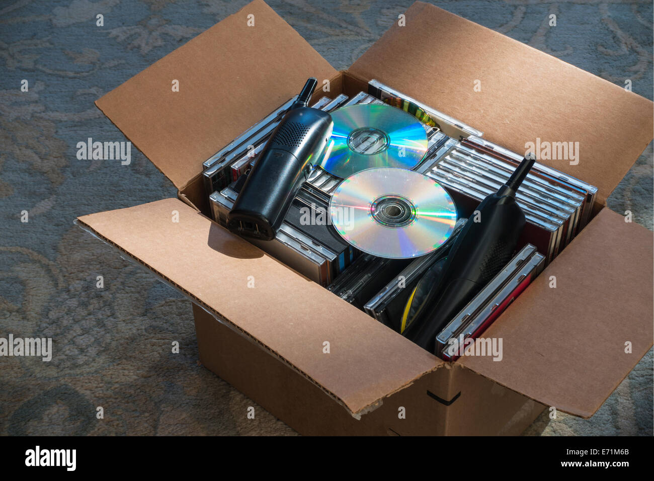old phones and obsolete CDs in carton - Stock Image