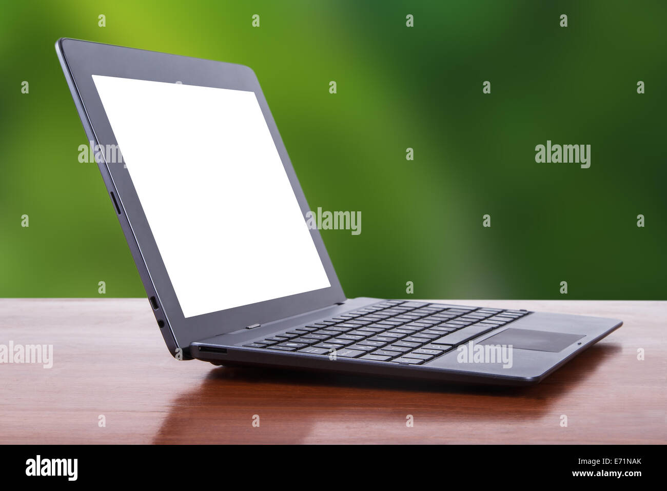Tablet laptop with white blank screen on wooden table, side view, green natural background. - Stock Image