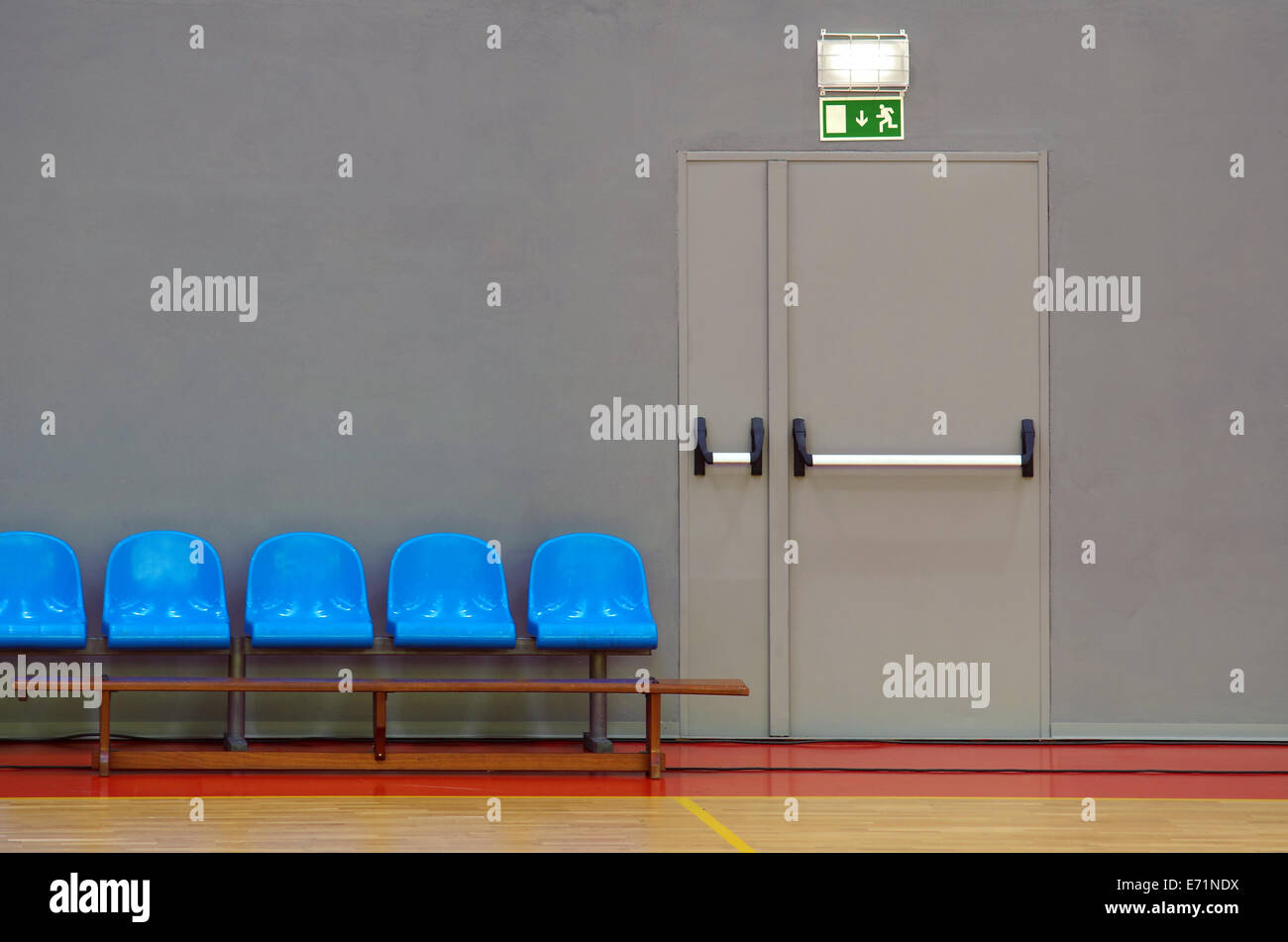 Emergency exit door next to a row of blue sits in a sports pavilion - Stock Image