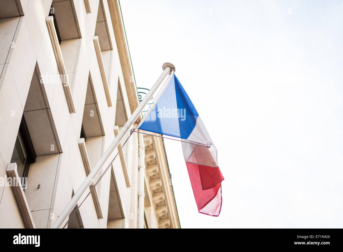 Flag of France fluttering on a pole placed on the top of a vintage building, under a serene blue sky with white - Stock Image